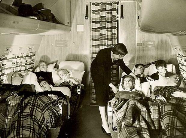 Parte interna do avião com pessoas deitadas em bancos espreguiçadeiras